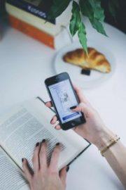קריינות מקצועית לסרטי הסברה - בחורה צעירה מביטה בטלפון תוך כדי קריאת ספר