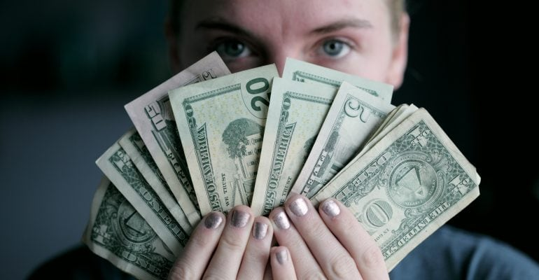 Things to Do When Seeking a Professional Voice Over - Woman holds Dollar bills