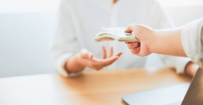 What is voice over - woman hands cash to another person
