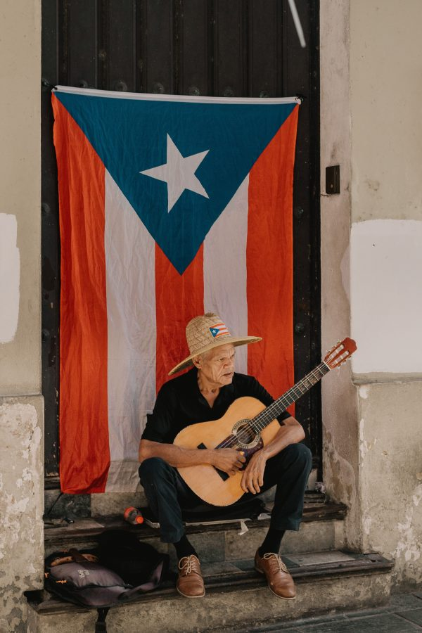 Puerto Rican Spanish voice actors - old man plays guitar with puerto rican flag behind
